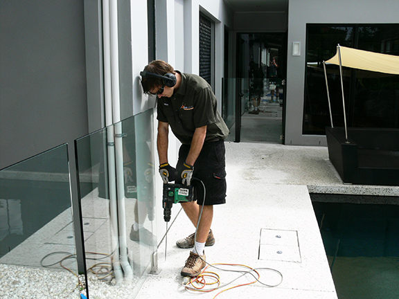 Drilling holes for termite barrier.